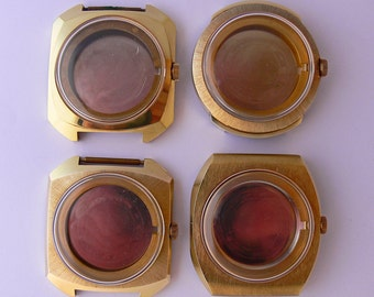 Set of four NOS brass watch cases . Complete with stainless steel back , plastic crystal and crown .