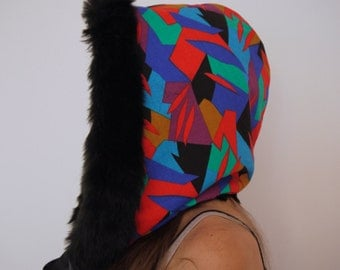 Multi coloured geometric pattern hood with ribbon ties.