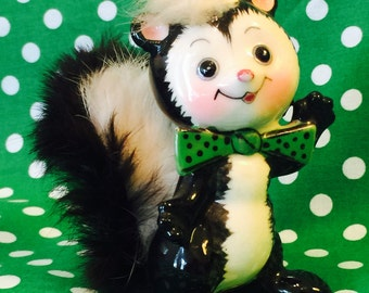 Ucagco Anthropomorphic Skunk Figurine with Green Polkadot Bow Tie and Fluffy Tail made in Japan circa 1950s