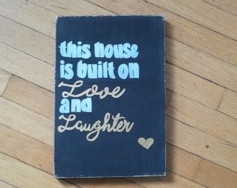 this house is built on love and laughter wooden sign