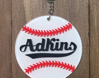 Personalized baseball acrylic keychain with white vinyl, red stitches, and black name.