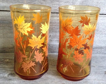 Set of 2 vintage amber colored autumn leaf drinking glasses with orange and yellow leaves.