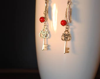 earrings decorated with a metal key and feather