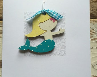 Hand painted birch plywood mermaid presented on a 13.5cm card. A card and gift in one.