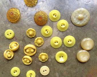 Mixed lot of 24 vintage yellow buttons, pierced, carved, sets and singles