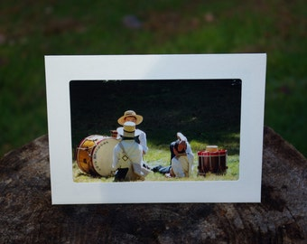 Photo mat card of a scene of young men in colonial outfits with blank inside for your note.