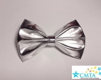 One silver faux leather hair bow. Portion of sale goes to charity. Cruelty-free.