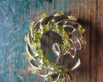 a pin or brooch with green stones...