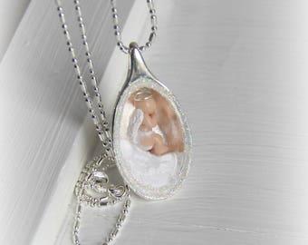 ON SALE! Tiny angel baby resting inside a silver pod necklace