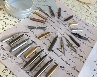 A set of one dozen of nibs, collection includes 13 different nib types in the set in a circular tin with perspex lid.