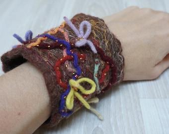 Felted bracelet wrist cuff arm warmer beaded bow flower floral botanical free form green burgundy brown orange seed purple yellow pink