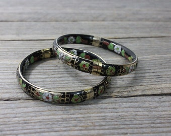 A pair of cloisonne bangle bracelets...red and green floral pattern on black background