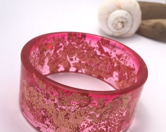 Handmade eco-resin wide bangle in pink with embedded copper leaf.