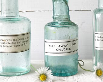A set of three original antique bottles with apothecary labels