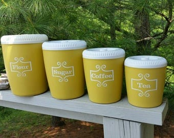 Yellow Canister Set Of  4 with with White Scroll Work Pattern Lables