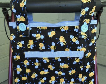 "Walker Bag. Walker tote. Bee themed walker tote bag. Yellow bees on black.  Blue lining. Front pocket. Velcro closure. Size 15"" W x 12"" D."