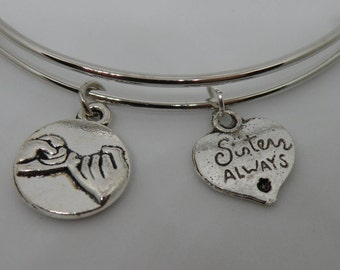 """Sister pinky swear silver bangle bracelet with a """"Sisters Always"""" and pinky swear charms."""