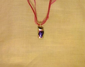 Hot pink and purple dichroic glass pendant on hot pink necklace.