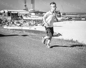 Candid urban street photography,Black White print, boy running on the prom, East coast England,  summer 2016, wall decor, fine art print