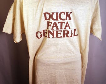 "Early 80s WEIRD ""Duck Fata General"" Screen Stars Graphic Text Soft T-Shirt Light Yellow Brown Sz L/XL Obscure Novelty Promo Made USA 50/50"