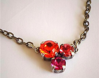 Delicate Swarovski crystal hyakinth and hot pink three -stone pendant necklace ,gunmetal plated setting