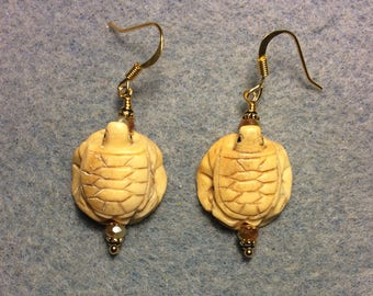 Carved bone turtle on a lily pad bead earrings adorned with beige Chinese crystal beads.