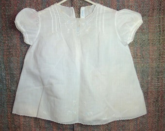 Vintage baby dress with pretty scalloped trim, embroidered and pleated front, puffy short sleeves. Tag 12 mo's Made in Philippines.