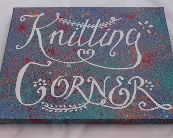 Knitting Corner Canvas for your creative space.  White hand lettering on Blue/Purple, with a green, orange and red splattered background.