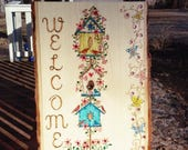 Welcome sign wood burned painted and embellished with crystals birdhouses flowers butterflies and vines