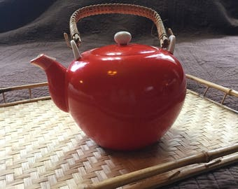 Orange teapot with wicker wrapped handle