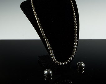 "Stunning! Necklace and earrings in hollow bead steel 22"" necklace and large clip-on earrings to match."
