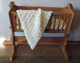 Crocheted cream baby blanket.