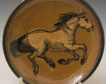 Horse painted and slip trailed on plate with honey amber glaze