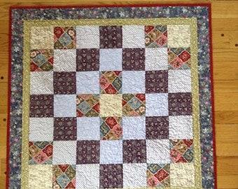 Patchwork baby quilt in shades of purple blue and red