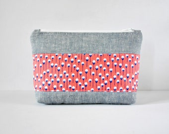 Woman's linen beauty padded travel bag coral pink and navy dandelion floral print panel cosmetics make up pouch in light grey.