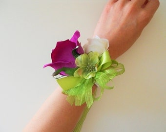Purple and ivory roses wrist corsage with green and rhinestone accent