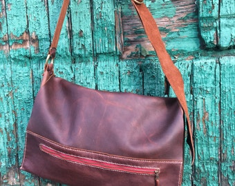 Hand stitched leather messenger bag, with pocket.