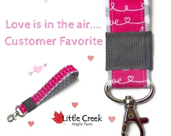 Pink script LOVE wristlet keychain on gray polka dot background, fuchsia key bracelet, hot pink and gray loop keychain, trendy key fob