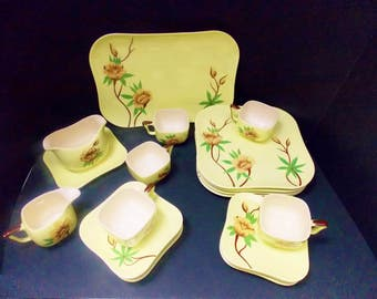 "Four place setting  square yellow dishes with green and brown accents  Weil Ware California pottery  ""Rose"" pattern  hand decorated"