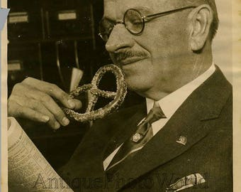 Man with glasses reading & eating a pretzel 1930s photo