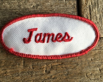 "James. A white work shirt patch that says ""James"" in red script with red border"