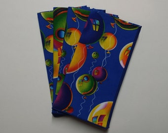 Set of 4 Party dinner napkins with multi colored balloons on blue.