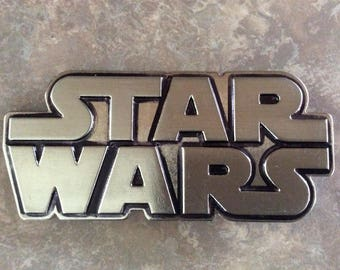 A Silver Metal Star Wars Belt Buckle with Black Lining.