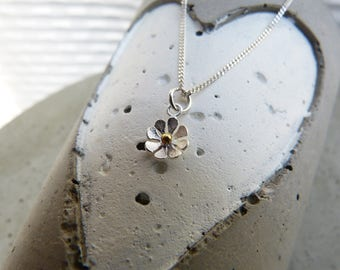 Delicate curb chain in sterling silver with a small flower pendant