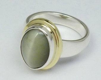 Silver, 14 carat gold, chrysoberyl cat eye ring. Sterling silver, 14 carat yellow gold and chrysoberyl cat eye cabochon solid ring.