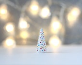 Little white clay Christmas tree with gold garland and red, teal and gold dots