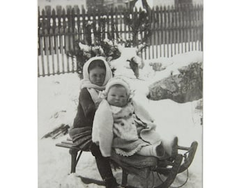Antique photo postcard of a young girl with her baby sister on a sled / sledge