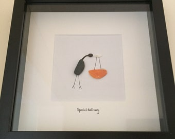 Handmade beach pebble art picture of a stork carrying a baby by special delivery. Unique new baby or baby shower gift.