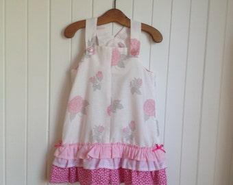 Size 3 Girls pink rose patterned summer frilled dress overall. Shoulder straps pink bows