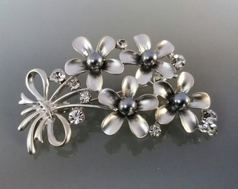 Metal flower brooch and gray beads